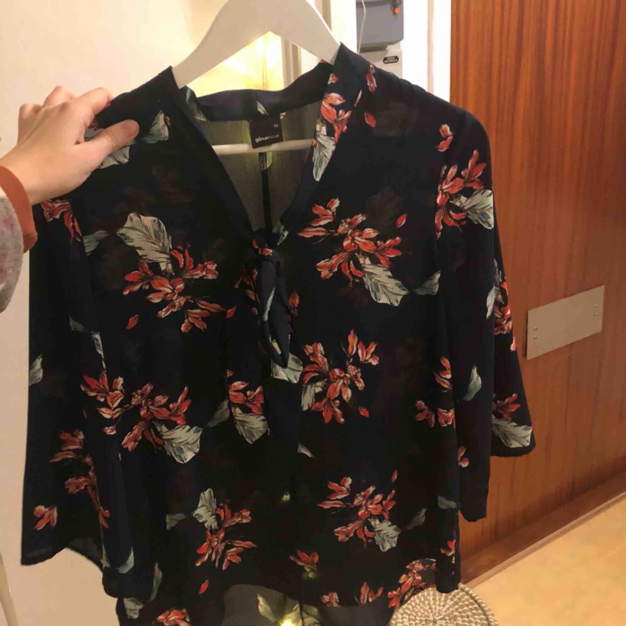 Blommig blus med knyte framtill, använd 1 gång, fint skick! Priset är inklusive frakt, betalning sker via swish💃🏽. Blusar.