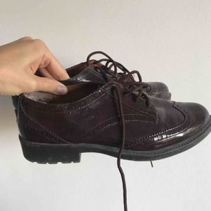 Skor från i London, dessvärre står ingen storlek, men de passar mig som brukar ha skor i storlek 38/39. Mörkröd färg och snören i samma färg, i glansigt material. Priset inkluderar inte frakt. Använda ca 1-2 gånger, men skicket är väldigt bra.