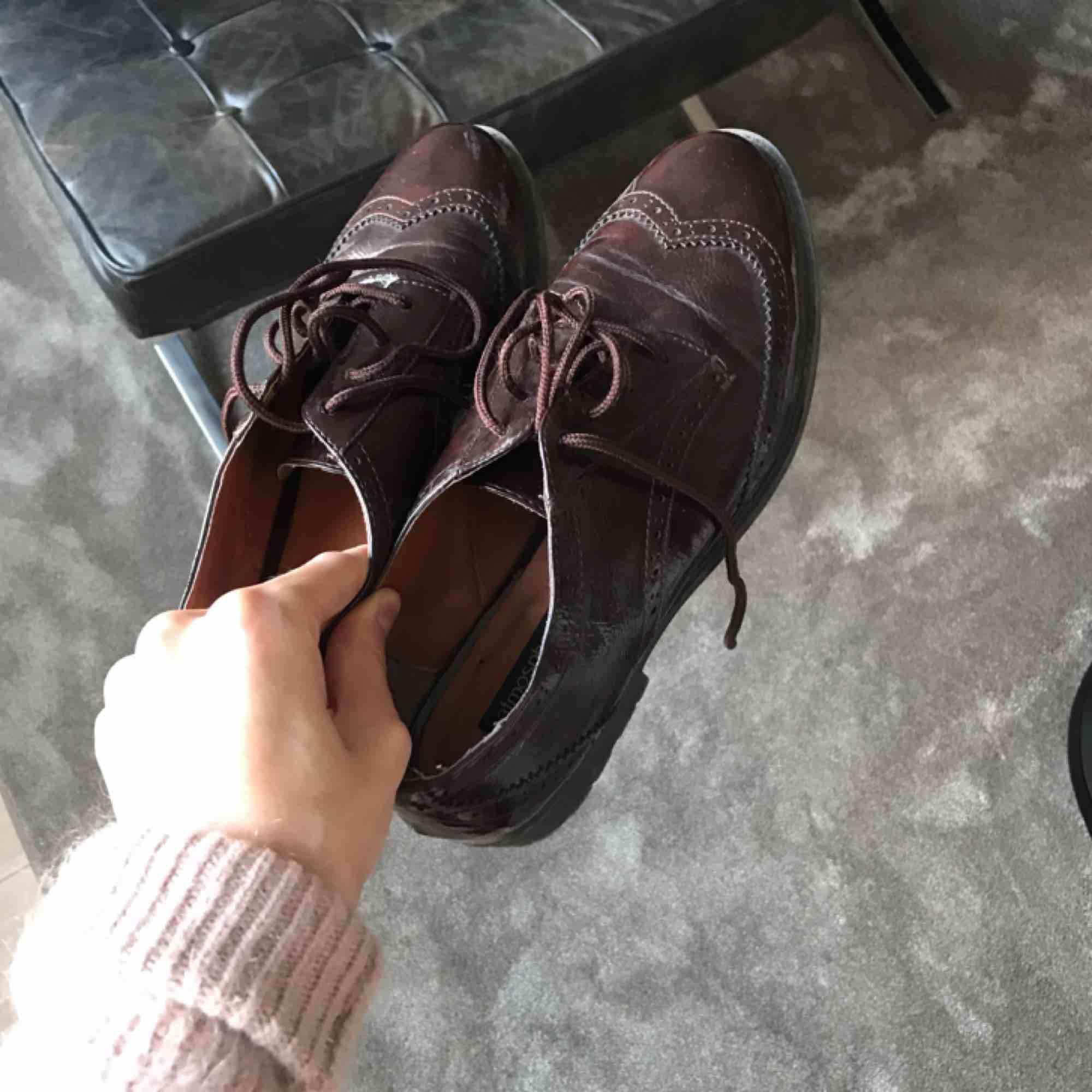 Skor från i London, dessvärre står ingen storlek, men de passar mig som brukar ha skor i storlek 38/39. Mörkröd färg och snören i samma färg, i glansigt material. Priset inkluderar inte frakt. Använda ca 1-2 gånger, men skicket är väldigt bra. . Skor.