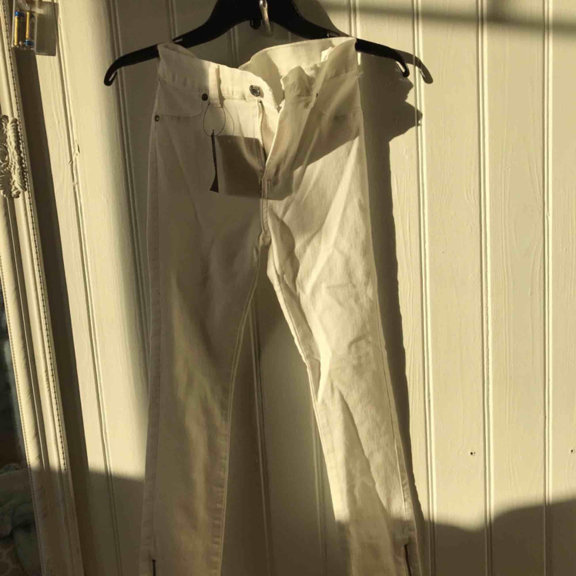 """Vita jeans från Dr.denim i modell """"Domino"""". Strl.S med dragkedjor längst ner & alla lappar sitter kvar. Så dom är helt oanvända, säljs billigt pga jag vill få bort dom då jag tycker det är synd att dom bara ligger här hemma. . Jeans & Byxor."""