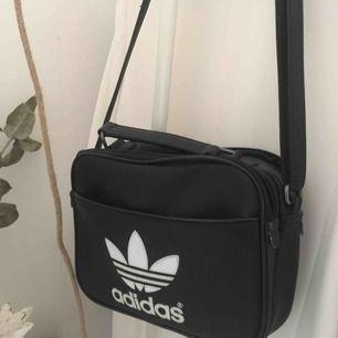 Adidas väska i fint skick! Justerbar axelrem och flera rymliga fack med dragkedjor.