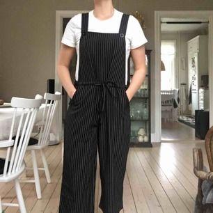 """Supersköna svarta hängselbyxor med vita ränder från det engelska designer märket """"he"""". Materialet är polyester"""
