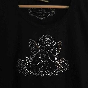svart t-shirt med en ängel, stretchig så passar i princip vem som helst, köpt second hand