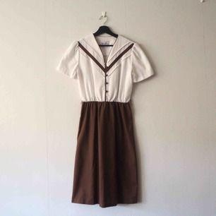 Vintage klänning köpt på vintage mässa. Vit, brun, knälång, V-ringad, kortärmad med små puffar, fyra knappar samt resår i midjan.