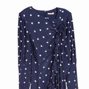 Blå vit prickig klänning med små axelvaddar och dragkedja där bak. Det finns knytning så att man själv kan reglera hur den ska sitta. Lapp kvar. Alltså aldrig använd. Frakt ingår i priset. Swish