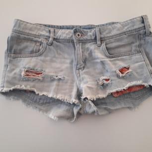 Jeansshorts med röda paisleymönstrade fickor stl 40 ganska väl använda men i bra skicka