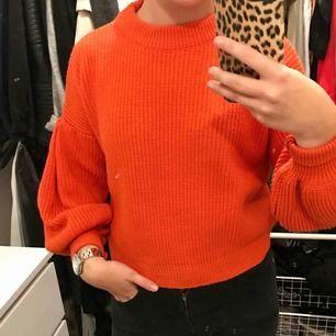En stickad tröja från Chiquelle, lite röd orange färg med ballong ärmar. Aldrig använd. Frakt tillkommer.