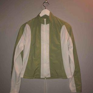 Grön och vit tunn jacka / tröja med dragkedja.