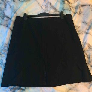 Svart kjol aldrig använd i storlek 52. Har en dragkedja på sidan och en slits.