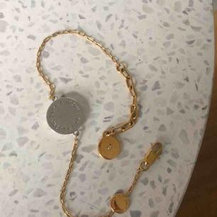 armband från marc jacobs med silverberlock och guldkedja. helt ny, aldrig använd.