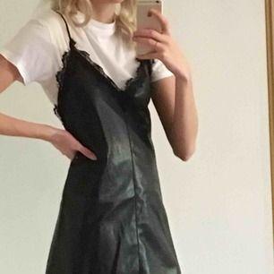 Cool klänning i skinnimitation! Den har tunna axelband och spets kring v-ringningen. Snyggt att bära med en annan tröja under eller utan!