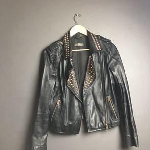 Svart skinnjacka från Zara med guldfärgade nitar. Står inte storlek men gissar på att det är en S-M