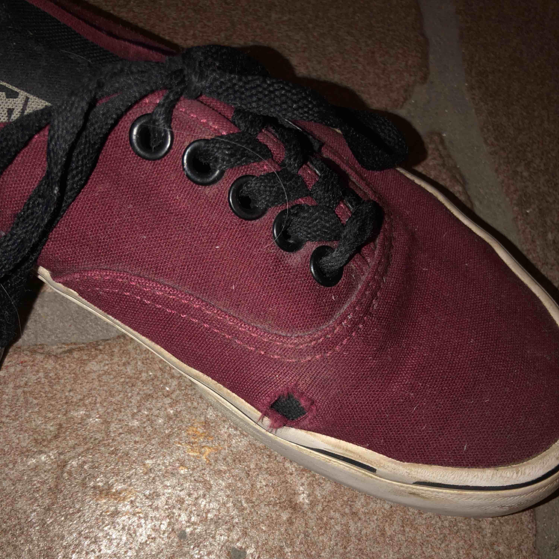 Vinröda vans, använda men ändå okej skick förutom slitningen på vänster sko. . Skor.
