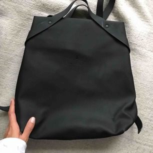 Gorgeous Rains backpack! Matte black, rubber feel. I only wore a couple times and then had to get a bigger bag that could fit all my yoga stuff :) There is a small rip inside lining of the back, but doesn't affect the functionality.