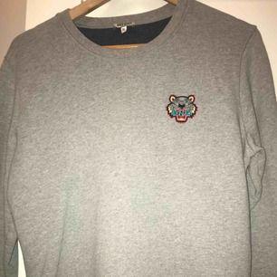 Superfin grå sweatshirt från Kenzo! Väldigt liten i strl så skulle säga att den är som en liten M (38) i strl. Kan mötas upp i stockholm eller inrikes leverans.