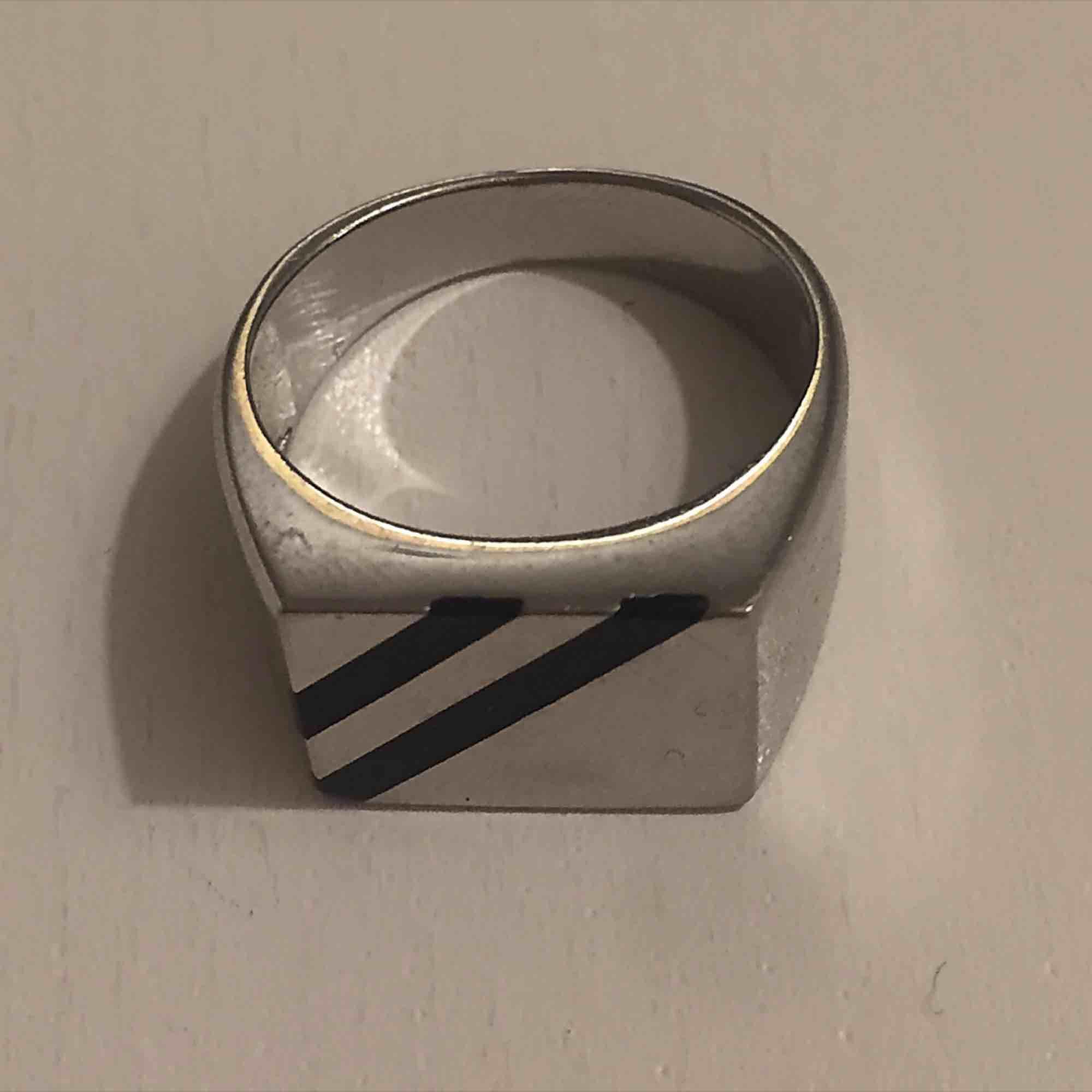 Silver plackerad ring med svart rand. Super snygg och färgar inte av sig!! Kan mötas i Sthlm eller skicka (köparen står för frakt). Accessoarer.