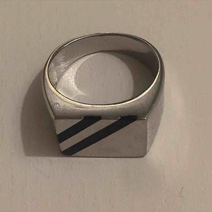 Silver plackerad ring med svart rand. Super snygg och färgar inte av sig!! Kan mötas i Sthlm eller skicka (köparen står för frakt)