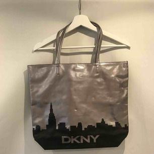 Supersnygg silvrig väska med svart stadssilhuett på från DKNY! Säljer eftersom den får alldeles för lite uppmärksamhet i min garderob. Möts upp i Stockholm eller så står köparen för frakt, tar swish!