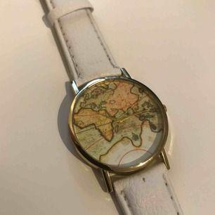 Fin klocka med världskartan på uret från okänt märke. Möts upp i Stockholm eller så står köpare för frakt, tar swish!