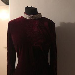Nelly klänning med pärlor runt halsen och runt handleden.  Strl 38. Oanvänd. Färgen är mörkröd.  Passar perfekt till julfirandet.