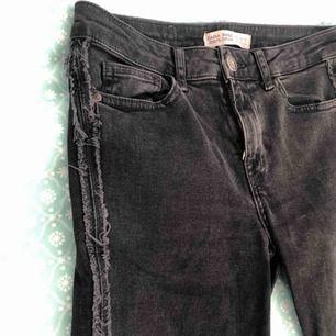 Gråa tajta jeans med detaljer på sidorna.