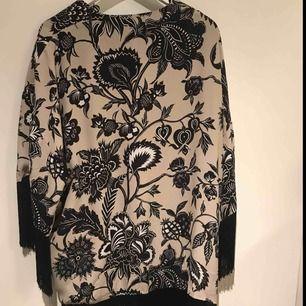 Sjal/cardigan med svarta fransar nertill Aldrig använd