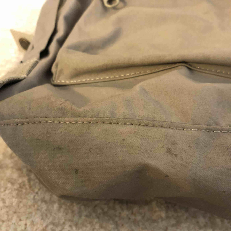 Grå fjällräven ryggsäck. Fint skick förutom lite smutsig i botten (se bild 2). Frakt ingår inte i priset. Nypris var 900 kr. Väskor.