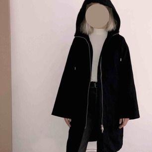 Svart, lång, kappa med luva, dragkedja och stora fickor. Ett år gammal men knappt använd, dvs i mycket gott skick. XS, men stor i storleken.