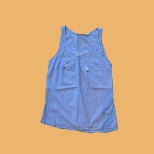 Ljusblå blus med snörning i 100% bomull!! Använd ett fåtal gånger. Säljer pga. för liten, frakt står köparen för❣️