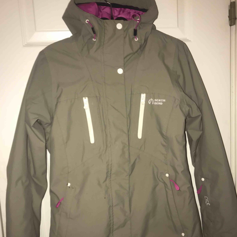 Skidjacka som är använd en vinter. Storlek 36. Finns lite defekter såsom att färg har lossnat från dem vita knapparna och små fläckar som nog går bort i tvätten. Jackan är i en mörkgrön färg med rosa detaljer, och rosa inuti.  350 + frakt . Jackor.