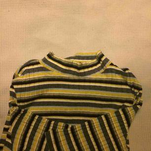 Randig t-shirt med lite längre ärm och liten turtleneck i använt men gott skick. Passar även medium.