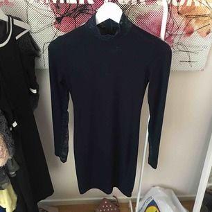 Marinblå klänning från Chiquelle. Tajt passform men stretchig. Spets liknande material på halsen och bakarmarna.