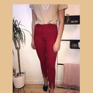 Röda jeans med sömmar längs framsidan av benet samt med slitsar. Aldrig använda.