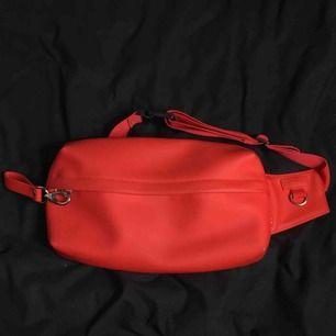 Röd Midjeväska från hm men's. Använd ca. 10 gånger, helt ny kvalité. Har flera fickor både utanför och innanför, mycket utrymme. Frakt är + 30kr