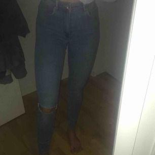 Blåa jeans med hål på ena knäet