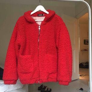 En röd fluff jacka som är använd endast en gång. Köpt för 400kr, säljs för 200kr.