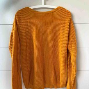 Senapsgul stickad tröja från NAKD, djup v-ringning i ryggen. Sparsamt använd, mycket fint skick.
