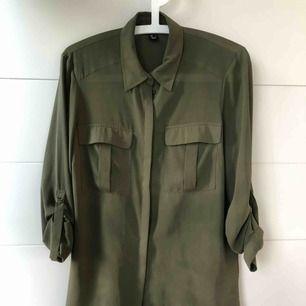 Militärgrön skjorta i fint fallande material, sparsamt använd, mycket fint skick.