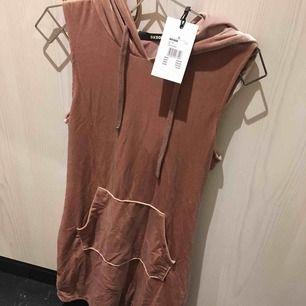 Jättesnygg klänning i streetmodell med huva! dusty pink/smutsrosa i  färgen. Oanvänd, prislappen kvar.