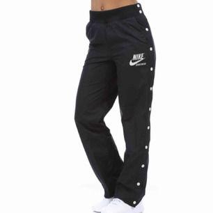 Ett par mörkblå/svarta track pants från Nike med vita knappar längs sidorna som går att knäppa upp. Storlek M, inköpta från Madlady och aldrig använda. Vid betalning: möts upp, betalningen sker via Swish.