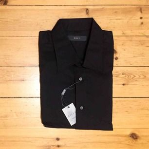 Helt NY svart skjorta från Riley, inköpt på Brothers för 499kr. Slim fit, långärmad, bra kvalitet.  Stl L 41/42  Har Swish. Kan skickas. Rökfritt & djurfritt hem.