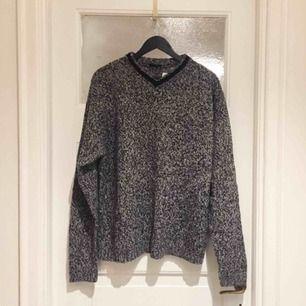 Helt NY tröja i 100% ull. Stickad i svart/vit/grå melerat garn och svart kant vid kragen. V-ringad.  Stl XL  Har Swish. Kan skickas. Rökfritt & djurfritt hem.