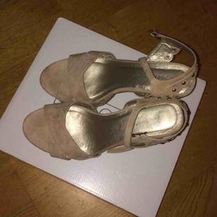 Ett par beiga klackskor med öppen tå och 12cm klack (inkl. 4cm platå). Använda endast en gång och är i mycket bra skick. De är köpta från Nilson Shoes och är från märket Depeche. Vid betalning: möts upp, tar endast Swish.