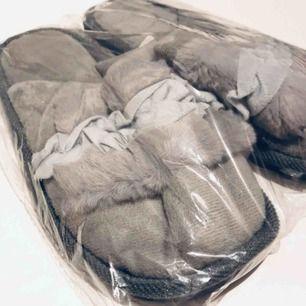 """Helt nya inomhustofflor, kvar i förpackningen. Grå med (fejk) päls pch """"volanger"""" i mitten. Har ett par i svarta som är jättefina och sköna, använder dagligen hemma!"""