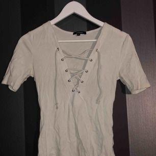 En fin vit t-shirt med snörning. Köpt på en butik i USA. Frakten är inräknad i priset. Så gott som ny.