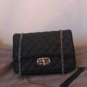 Superfin svart väska från Nelly, är lite mjukare i modellen. Passar både till vardags och fest.