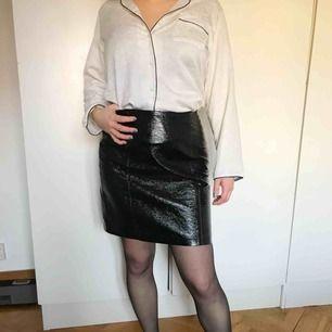 Kort, midjehög kjol i glansigt fakeskinn. Använd en gång. Köparen står för frakt alternativt möts upp i Uppsala.