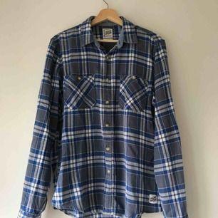 Blå och vitrutig skjorta i bomull. Köpt second hand. Är använd, men i gott skick.