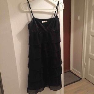 Svart klänning med paljettdetaljer och volanger.