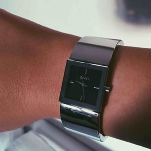En fyrkantig silver klocka från DKNY. 21mm. Rostfritt stål. 3 ATM. Behöver ett byte av batteri. Frakt exkl. från priset, betalas av köparen.